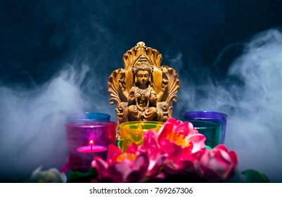 Hindu goddess Lakshmi. Statue with a smoke, candles and lotus flowers on a black background