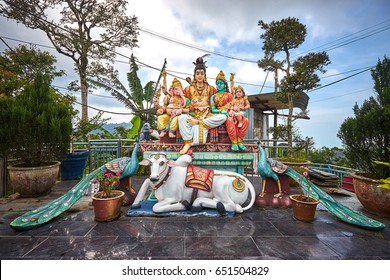 Hindu gods Shiva, Parvati, Ganesha and Murugan sitting on the throne with white sacred cow and two peacocks below. Statue at Sri Aruloli Thirumurugan Temple.