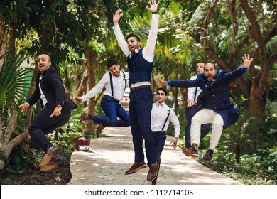 Hindu groom and groomsmen have fun jumping outside in the garden