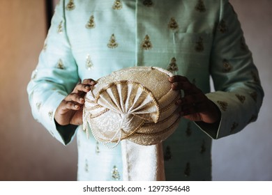 Hindu groom holds his wedding hat in the arms