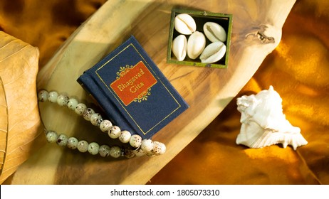 Hindu Holy book 'Bhagvad Gita' kept on a wooden base with dry leaf and other spiritual props   - Shutterstock ID 1805073310