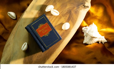 Hindu holy book and cowrie shell on a wooden surface with golden satin cloth  - Shutterstock ID 1805081437
