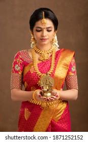 Hindu Indian young bride holding Deepa in studio shot.