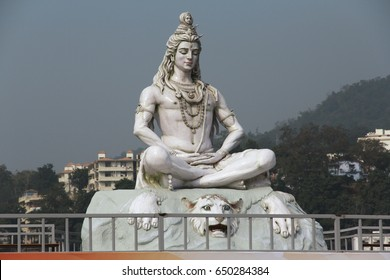 Hindu lord Shiva sculpture, god statue sitting in meditation on Ganges river in Rishikesh, India, 2011