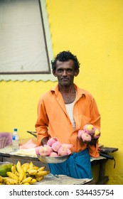Hindu man offering orange apples on the street in India. Vendor sells fruit. Journey through India.
