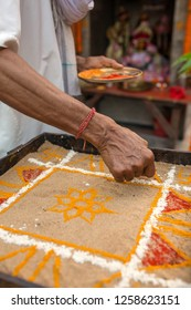 Hindu priest coloring traditional sand art (Rangoli) with religious pattern using colors from natural pigments like sindoor, haldi (turmeric)