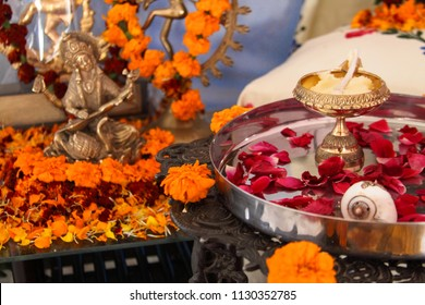 Hindu puja. Incense, offerings, rose petals, marigold flowers, goddess Saraswati and god Shiva statues. Traditional, indian, religion, holiday, Navratri, still life, south asian.