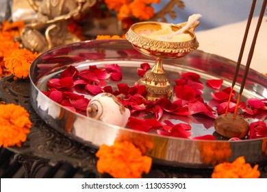 Hindu puja, offering to gods. Incense, rose petals, marigold flowers, goddess Saraswati figure. Traditional, indian, altar, religion, holiday, Navratri, still life, south asian.