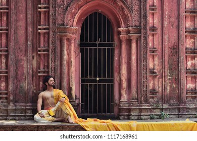 A hindu pujari or worshiper from ancient India is siting in front of a terra cotta walls of a temple of lord Shiva Indian lifestyle