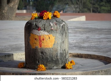 Hindu religious Shiva symbol lingam with colorful flowers resembling a painted face