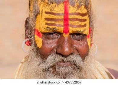 Hindu sadhu holy man, sits on the ghat, seeks alms on the street in Jaisalmer, Rajasthan, India . Close up