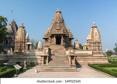 Hindu temple, built by Chandela Rajputs, at Western site in India's Khajuraho. Beige brown heap of stones artfully stacked against blue skies.