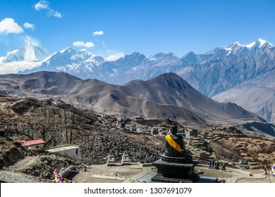 Hindu temple, Muktinath Mandir, surrounded by high Himalayan mountains, Annapurna Circuit Trek, Nepal. Buddha statute with orange ribbon looking at the mountains. Sacred place, pilgrimage destination