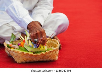 In hindu temple priest mangku praying and making offerings ritual before traditional Balinese New Year and silence day Nyepi. Holidays, festivals, art, culture of Indonesian people and Bali island.