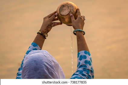 Hindu woman offering water to the Ganges river as part of an early morning ritual at Varanasi  Ghat India.