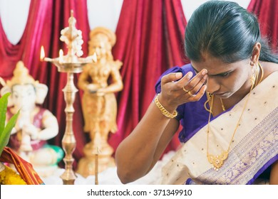 Hindu woman putting bindi or marking on her forehead during Indian traditional religious rituals, the tradition of Hinduism.