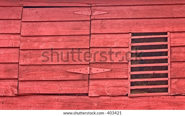 Hinged door and wooden vent to a hay loft in an old red barn in Gettysburg, PA.