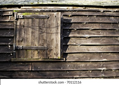 hinged window or door in an old wooden barn