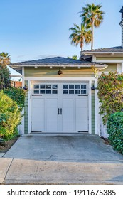 Hinged wooden garage door with glass panes and hip roof in San Diego California