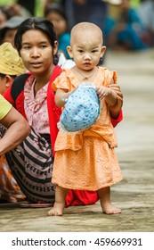 HINTHADA, MYANMAR - AUG 28:  Unidentified  Burmese kid daubs tanaka on her face on Aug 28, 2015 in Hinthada, Ayeyarwady (Irrawaddy) Division, Myanmar.