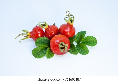 Hip berry. Four ripe red dog rose with leaves. Giant Berries Hips, isolated, on white background.  Isolated, on white background.