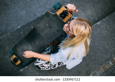 Hip girl sitting on stairs holding longboard