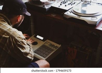 A hip hop composer, beatmaker creates beats on a digital production controller with pushbutton pads. The DJ plays the beats live on the pad controller of digital audio equipment. Rap music