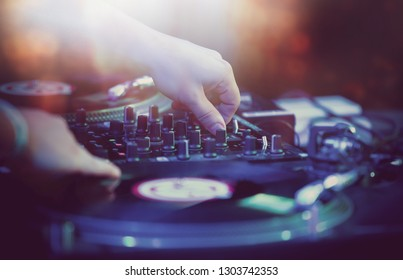 Hip hop concert dj plays set on night club stage in bright lights.Hands of disc jockey on vinyl record player and sound mixer panel.Musician playing rap music on festival in nightclub