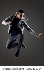 hip hop dancer jumping against gray background