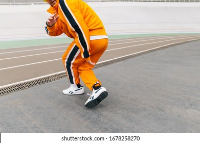 Hip hop dancer in trendy street clothes dancing on the stadium sports track. Street dancing concept. Stylish man dancing modern dance. Copy space. Hip hop background