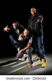 Hip hop dancers posing over a dark background