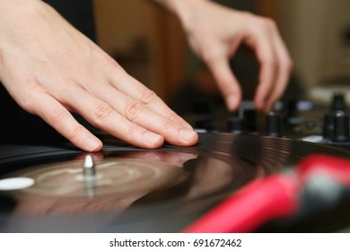 Hip hop disc jockey scratching vinyl records on turntables player in dj school.Hands of dj scratch record on retro turntables vinyl player.Professional disc jockey technology.Dj mix music tracks live