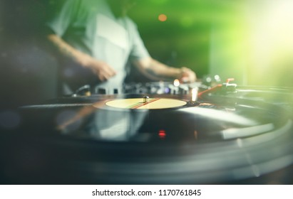 Hip hop dj plays retro vinyl recrods with hip hop music on concert in night club. Bright green stage lights.Professional audio equipment.Disc jockey scratches disc with musical tracks