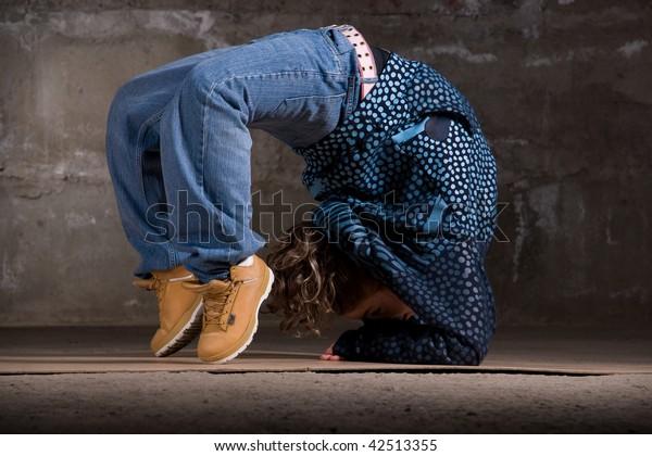 Hip hop girl dancing in modern style over urban grey brick wall