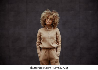 Hip hop girl in tracksuit standing with hands in her pockets and listening music.