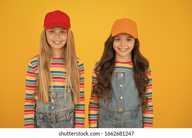Hip hop girls. Little girls smiling on yellow background. Happy small girls wearing baseball caps in casual style. Adorable caucasian girls with long loose hair.