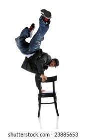 Hip hop man performing dance standing on chair