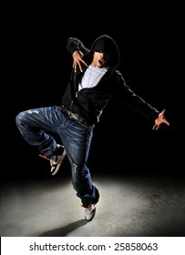 Hip hop style dancer with hood over a dark background with spotlight