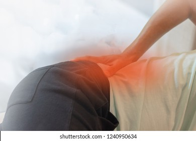 Hip joint pain concept. Man hand on his low back with red spot as suffer from injury or cancer of the spinal cord, a ruptured or herniated disc, sciatica, arthritis, kidney infections, spine infect.