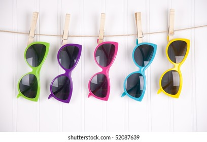 Hip summer sunglasses hanging on a white clothesline.