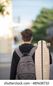 Hip teenager wearing a backpack and holding a longboard, view from behind.