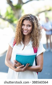 Hip woman holding notebook and smiling at the camera in the city
