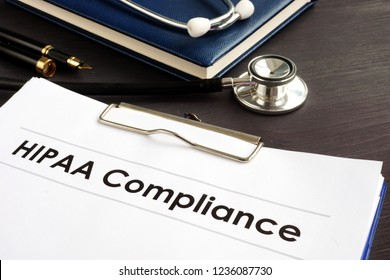 HIPAA Compliance documents with clipboard on a desk.