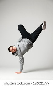 hip-hop dancer standing on one hand over grey background
