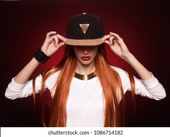 hip-hop girl in cap with long red hair. Fashion portrait of modern young woman in cap