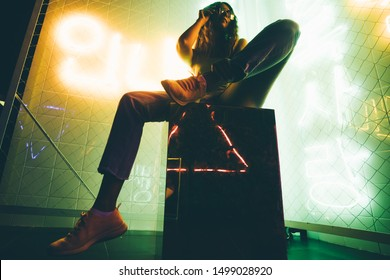 Hip-hop girl with longbord in cap at the neon light. Fashion portrait of modern young woman in cap and sunglasses.