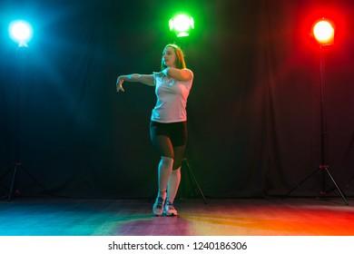 Hip-hop, jazz-funk, tecktonik, waacking, trance and street dances concept - Pretty woman dancing jazz funk over dark background