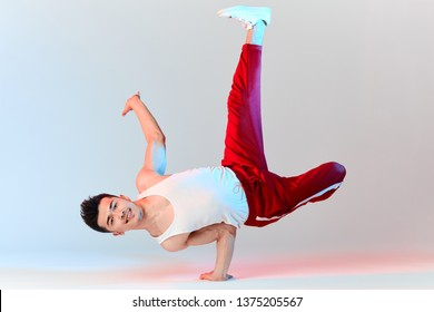 Hip-hop Korean break dancer in red sweat pants stay in white classroom all day and learn choreography done by other people, working out over technique. BBoy doing Chair Classic Freeze