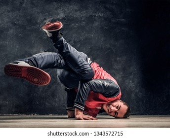 8457a4cc3695 Hip-hop style dancer performs breakdance acrobatic elements. Studio photo  against a dark textured