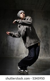 hip-hop style dancer posing on a grunge wall background